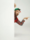 The happy smiling friendly man dressed like a funny gnome or elf posing on an isolated gray studio background. The winter, holiday, christmas concept - 232999043