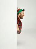 The happy smiling friendly man dressed like a funny gnome or elf posing on an isolated gray studio background. The winter, holiday, christmas concept - 232999097