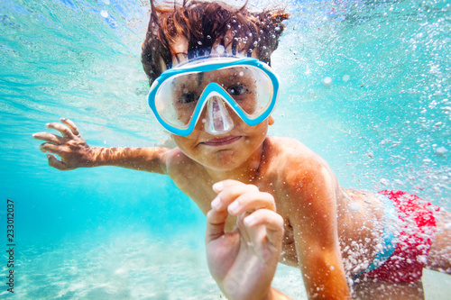 Leinwandbild Motiv Happy boy in scuba mask swimming underwater