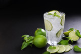 Fresh lime soda in glass drink with sliced lime on black background