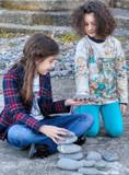 Coppia di bambine che giocano con dei sassi - 233020806