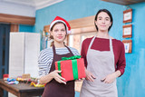 Waist up portrait of two young women wearing apron posing in art studio holding Christmas presents, copy space - 233027257