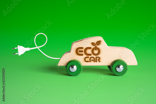 Wall mural Electric eco-friendly car concept. Wooden toy car with electric plug and charging cable. Words Eco Car impressed on the side.