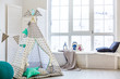 Stylish modern children room. Kid's wigwam in children room. Large wooden star lamp. Interior scandinavian style.