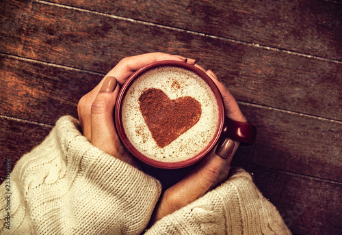 Leinwandbild Motiv woman holding hot cup of coffee with heart shape symbol. Above view