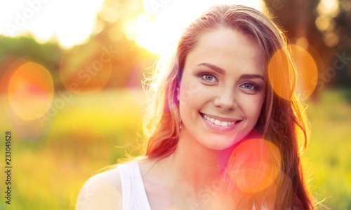 Foto Murales Young woman on field under sunset light