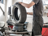 Wheel whit winter tire on tire changing machine in a workshop. Wheel on tire changing machine.