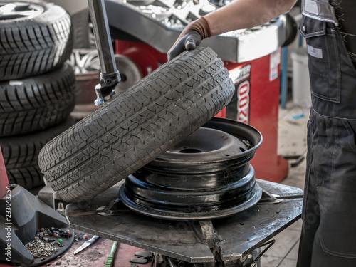 fototapeta na ścianę Wheel whit summer tire on tire changing machine in a workshop. Wheel on tire changing machine.
