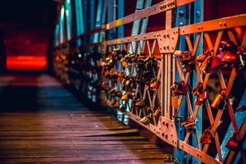 Padlocks hanging on a bridge fence as symbol of love and friendship forever. European youth romance culture concept © madrolly