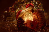 Fototapety Family open Christmas Lighting Present Gift Box front of Xmas Tree, Happy Mother with Baby Child in Magic Night
