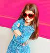 Leinwandbild Motiv Beautiful portrait little girl child in red heart shape sunglasses on colorful pink background