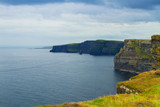 Photo of beautiful scenic sea and mountain landscape. Cliffs of Moher, west coast of Ireland, Atlantic ocean. View of ocean scenery
