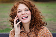 Quadro jeune et jolie femme rousse téléphonant avec téléphone portable dans un parc