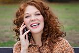 jeune et jolie femme rousse téléphonant avec téléphone portable dans un parc  © mariesacha