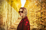 Style girl in sunglasses and red coat in Versailles park, France - 233081286