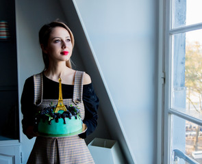adult girl holding a cream cake with Eiffel tower on it near window