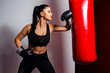 Attractive female boxing workout, punching bag with elbow