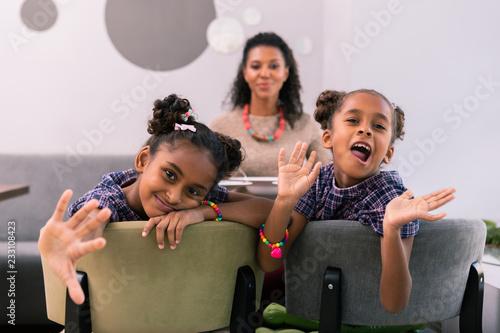 Wspólna zabawa. Stylowe szczęśliwe rodzeństwo beaming sobie jasne bransoletki i fioletowe kwadraty sukienki zabawy razem