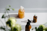 Clear plastic and glass brown bottles with organic cosmetics from above. Direct light. Beauty blogging minimalism concept - 233123043