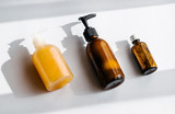 Glass brown bottles with organic cosmetics overhead. Direct light. Beauty blogging minimalism concept - 233123243