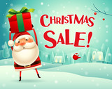 Christmas Sale! Santa Claus holds up gift present in Christmas snow scene winter landscape. - 233157899