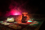 Arabian tea in glass with eastern snacks on a carpet on dark background with lights and smoke. Eastern tea concept. Empty space. - 233165695