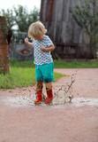 Petit bébé blond saute dans une flaque d'eau © Irena Begusic