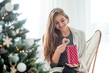 Young beautiful woman eating Christmas biscuits in bright room