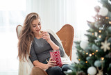 Young beautiful woman eating Christmas biscuits in bright room - 233179011