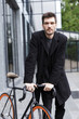 Handsome young business man walking outdoors with bicycle.