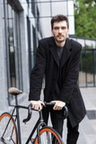 Handsome young business man walking outdoors with bicycle. - 233179813