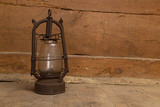 An old, kerosene lamp standing on a wooden floor against the backdrop of a wall made of planks. - 233182002