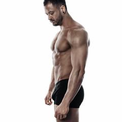 Brutal strong bodybuilder athletic man posing on white background. © Akaberka