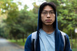 Image of young asian guy in casual wear and eyeglasses looking at you, while walking through green park