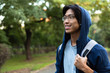Image of positive asian man in casual wear and eyeglasses smiling, while walking through green park