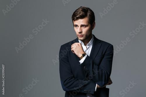 Wizerunek brunetka biznesmen 30s w czarnej kurtce patrząc na bok, na białym tle nad szarym tle