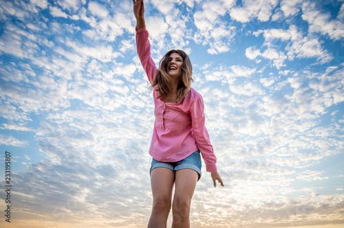 Dziewczyna w koszula macha jej ręki przeciw niebu z chmurami