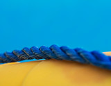Close-up of blue marine twisted rope on yellow lifebuoy, shallow dept of field - 233199009