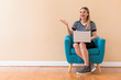Young woman with a laptop computer in a chair