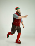 The happy smiling friendly man dressed like a funny gnome or elf pointing to left on an isolated gray studio background. The winter, holiday, christmas concept - 233210291