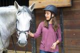 Beautiful Teenager Riding a Horse - 233210428