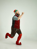The happy smiling friendly man dressed like a funny gnome or elf running on an isolated gray studio background. The winter, holiday, christmas concept - 233210432