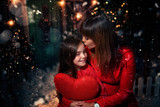 mom gives her daughter a kiss on a festive evening - 233210619
