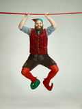 The happy smiling friendly man dressed like a funny gnome or elf hanging on an isolated gray studio background. The winter, holiday, christmas concept - 233210812