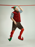 The happy smiling friendly man dressed like a funny gnome or elf hanging on an isolated gray studio background. The winter, holiday, christmas concept - 233210894