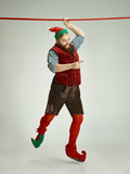 The happy smiling friendly man dressed like a funny gnome or elf hanging on an isolated gray studio background. The winter, holiday, christmas concept - 233211013