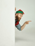 The happy smiling friendly man dressed like a funny gnome or elf pointing to left on an isolated gray studio background. The winter, holiday, christmas concept - 233211613