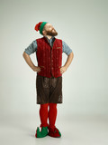 The happy smiling friendly man dressed like a funny gnome or elf posing on an isolated gray studio background. The winter, holiday, christmas concept - 233212247