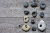 sellection of interesting shaped pebbles on rustic wood background - 233216205