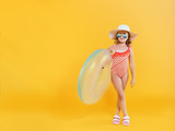 A little child girl in a hat and sunglass is holding a lifebuoy. Yellow background. Leisure and travel concept. - 233226895